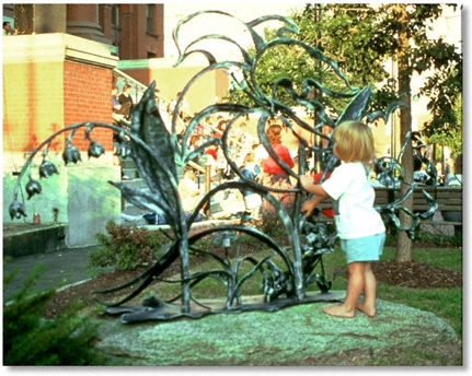 Little girl with park sculpture